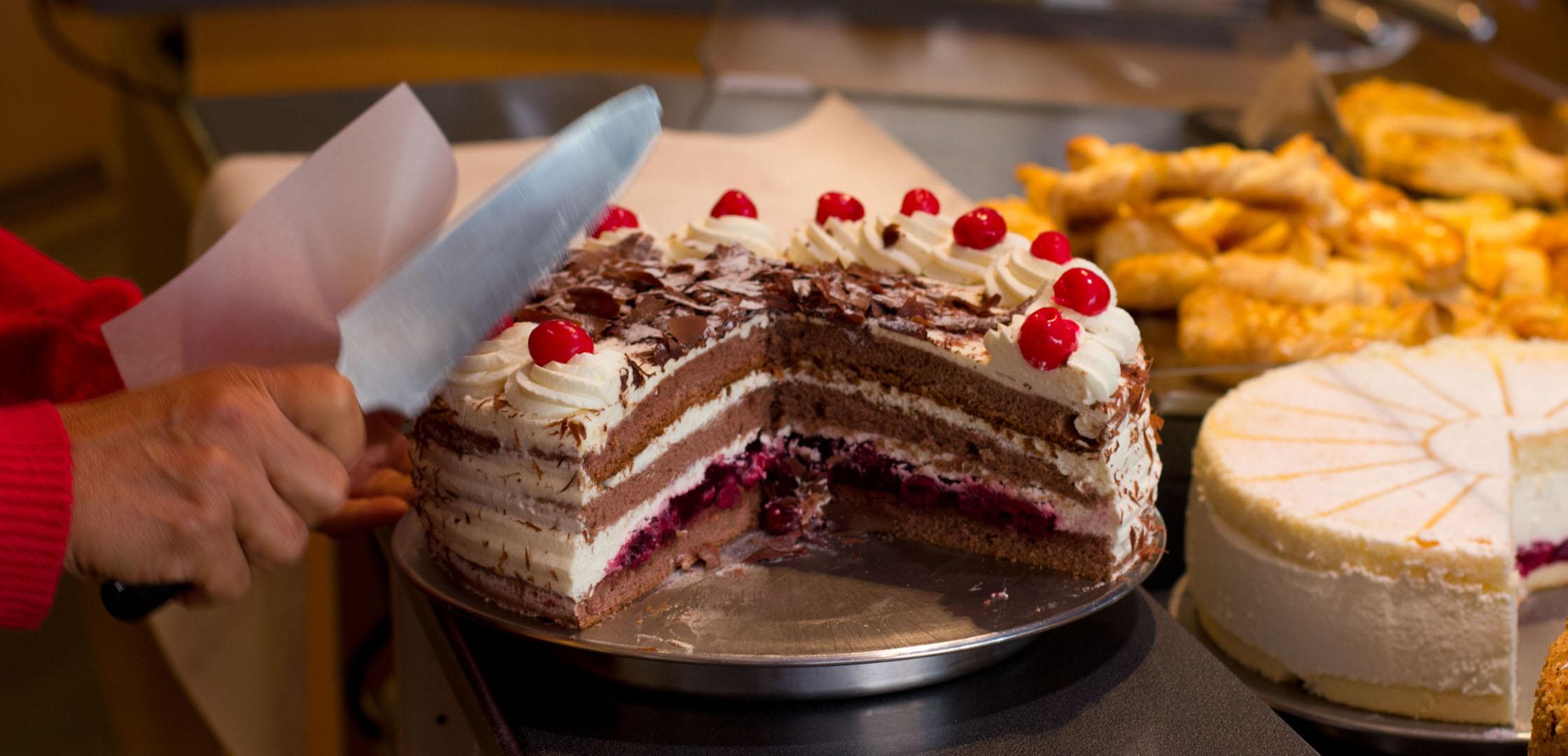 Eine Schwarzwälder-Kirsch-Sahne-Torte wird angeschnitten