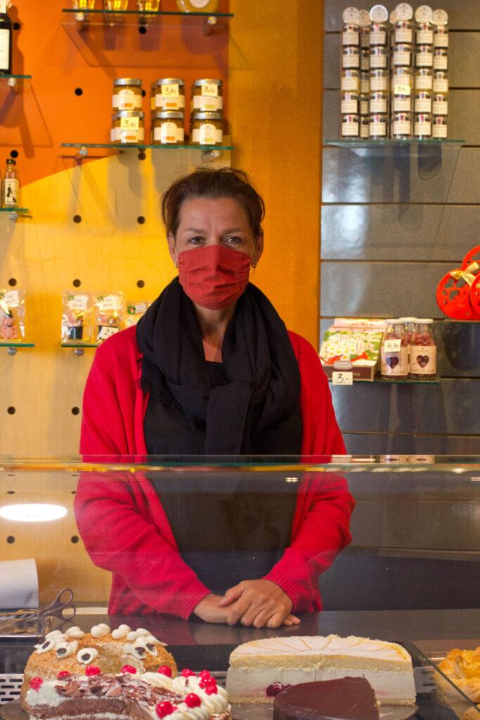 Kerstin Siebenhandl mit MNS-Maske hinter der Tortentheke